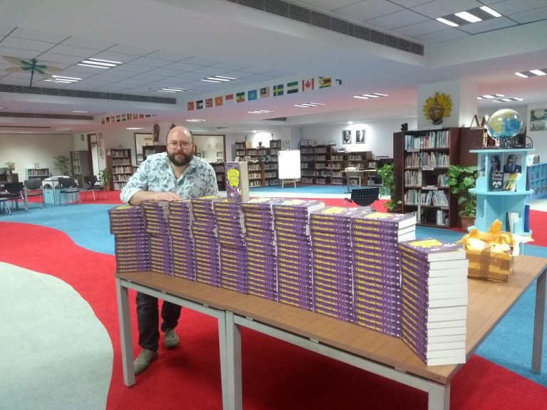 P.G. Bell posing with copies of The Train To Impossible Places in the library of Pathways School, New Delhi