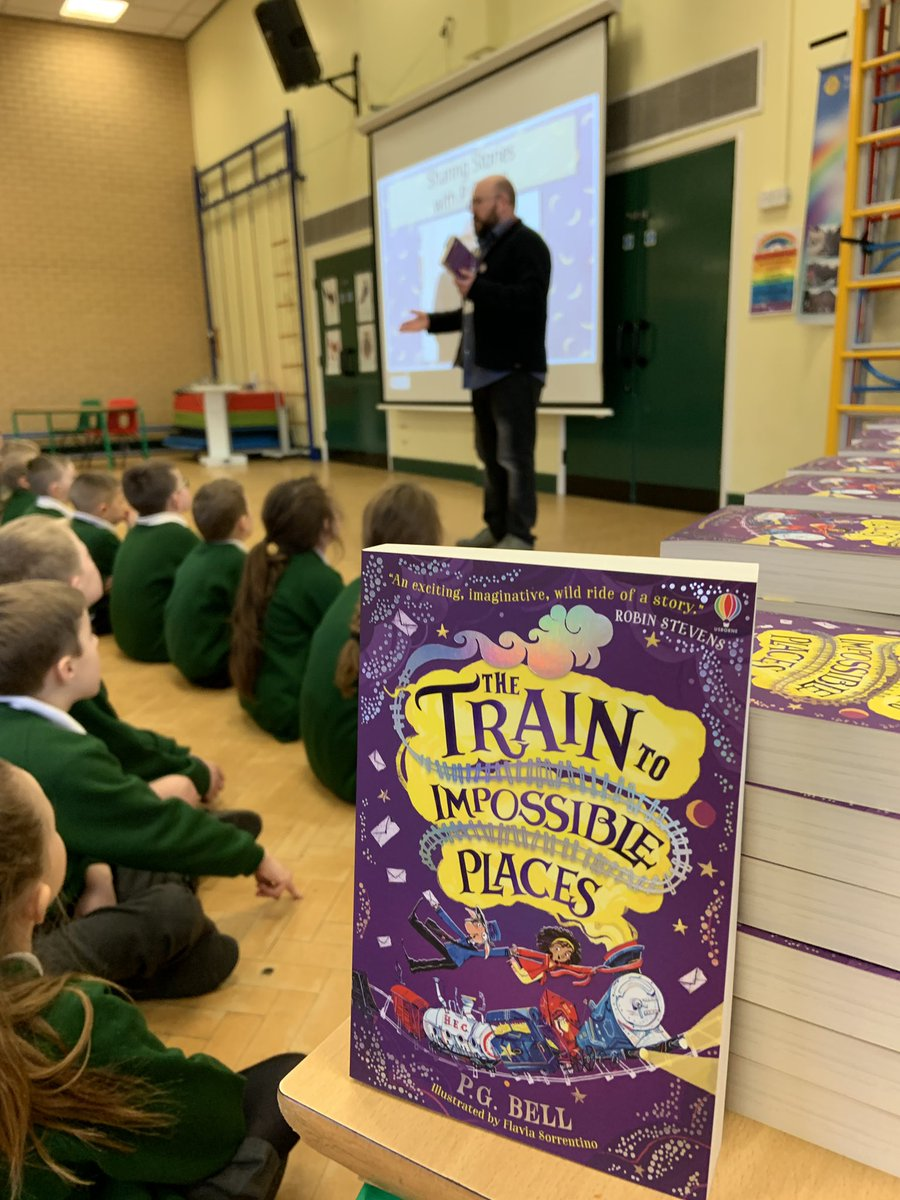 P.G. Bell addresses a school assembly with a copy of The Train To Impossible Places in the foreground