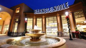 The exterior of a Barnes & Noble store at dusk, with a fountain
