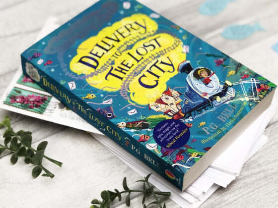 A copy of the UK edition of Delivery to the Lost City, sitting on top of a pile of envelopes on some wooden boards