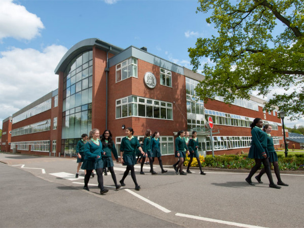 A view of the exterior of Haberdashers' Girls School on a sunny day. A group of girls in school uniform are walking together in the foreground of the shot